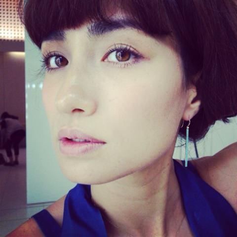 細いピアスをつけているブルーのトップスを着た佐田真由美の画像